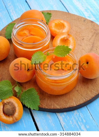 Ripe apricots with jam in glass jar. - stock photo