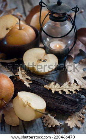 Ripe asian pears, lantern with candle and fall leaves on wooden table. Autumn concept. Selective focus. - stock photo