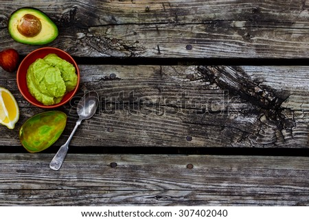 Ripe avocado and guacamole over rustic wooden background. Space for text. Top view. Food or cooking concept. - stock photo