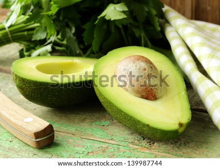 ripe avocado cut in half on a wooden table - stock photo