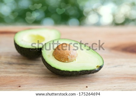 ripe avocado halves against a green background