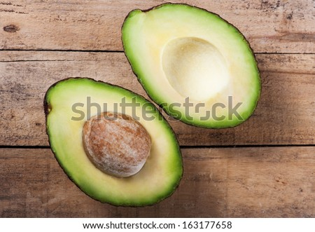 Ripe avocado on a wooden board in the studio - stock photo