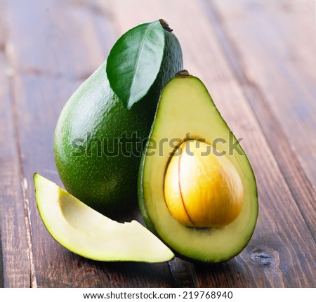 Ripe avocado on a wooden table. - stock photo