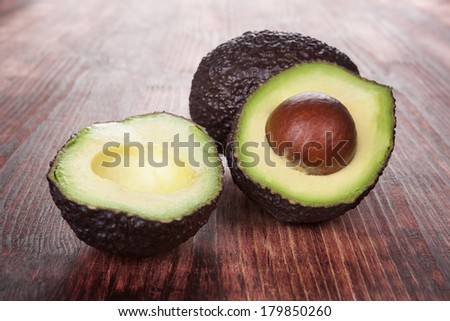 Ripe avocado on wooden background. Culinary healthy fruit eating. - stock photo