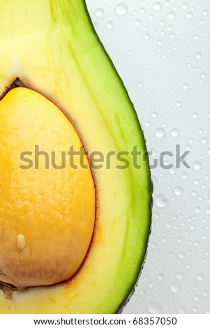 Ripe avocado with drops of water - stock photo