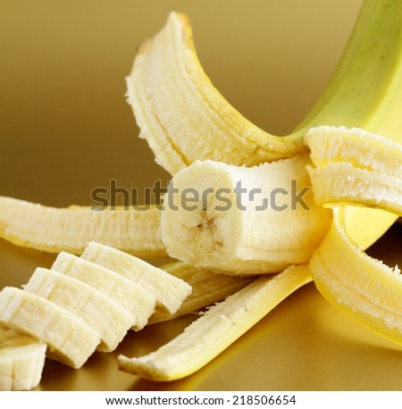ripe banana cut into slices on a gold background - stock photo