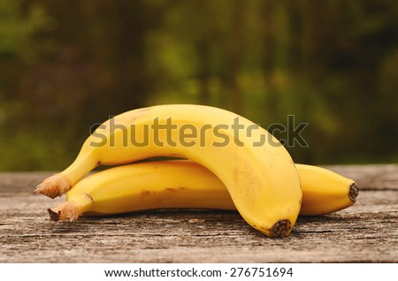 Ripe banana on a wooden background, detail - stock photo