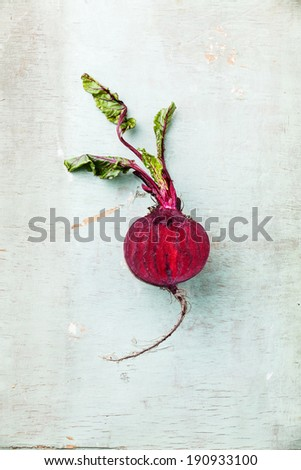 Ripe beet with leaves on textured background - stock photo