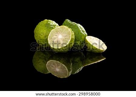 Ripe bergamot fruit on black background. Culinary cooking ingredient, tropical fruit bergamot orange. - stock photo