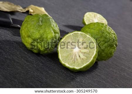 Ripe bergamot fruit on black background. Culinary cooking ingredient, tropical fruit bergamot orange - stock photo
