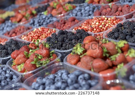 ripe berries in a plastic container in the store - stock photo