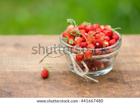 Ripe berries of wild strawberries in glass bowl. On wood background, closeup. - stock photo
