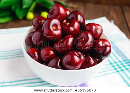 Ripe black cherries in a white bowl on a light background. Close-up.