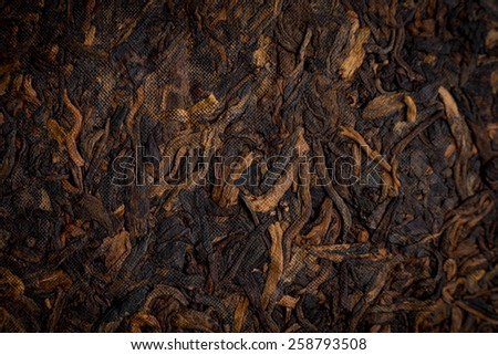 ripe black tea pancake Puer tea leaves close-up - stock photo
