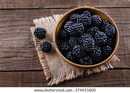 Ripe blackberries in a ceramic bowl on burlap cloth over wooden background close up. Rustic style, Selective focus - stock photo