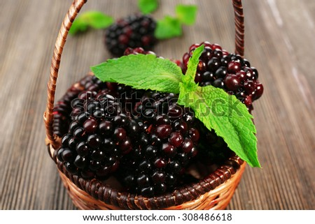 Ripe blackberries with green leaves in wicker basket on wooden table, closeup - stock photo