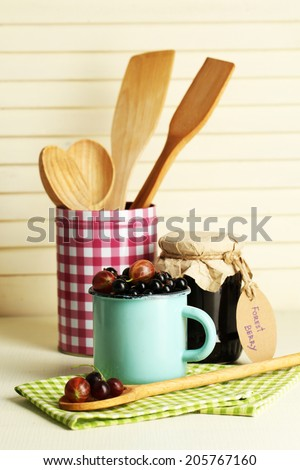 Ripe blackcurrants in mug and glass jar with tasty jam on light wooden background. - stock photo