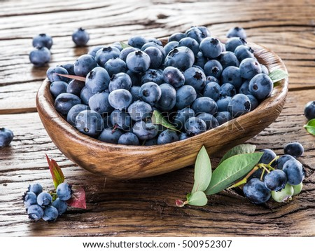 Ripe blueberries in the bowl on the wooden table.