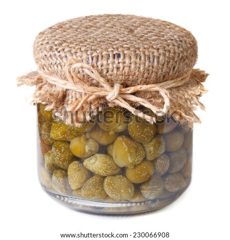 ripe capers in a glass jar closeup isolated on white background  - stock photo