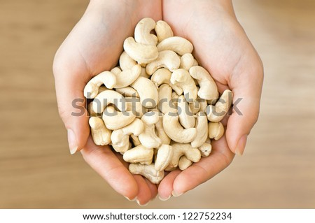 Ripe cashew nuts in woman's hands - stock photo