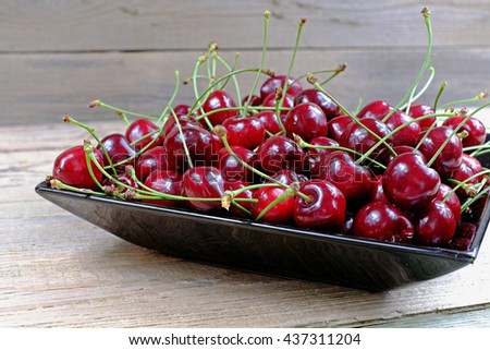 Ripe cherries in black porcelain plate on a old wooden table, fruit, red. pile - stock photo
