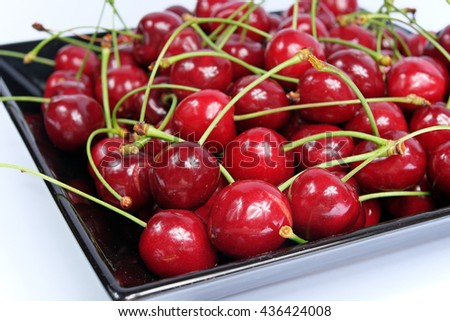 Ripe cherries in black porcelain plate on a white background isolated - stock photo