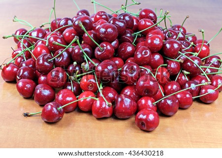 Ripe cherries on a wooden table - stock photo