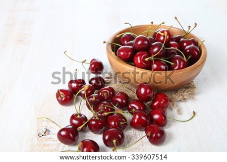 Ripe cherry in a wooden bowl on the table - stock photo