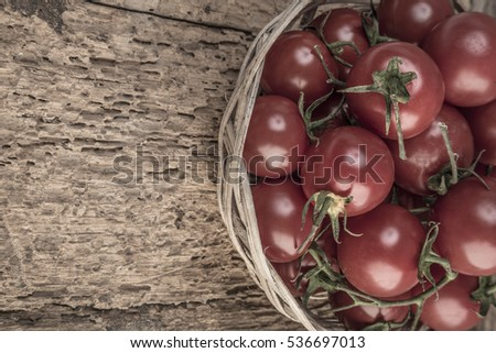 Ripe cherry tomatoes in a basket on wooden table