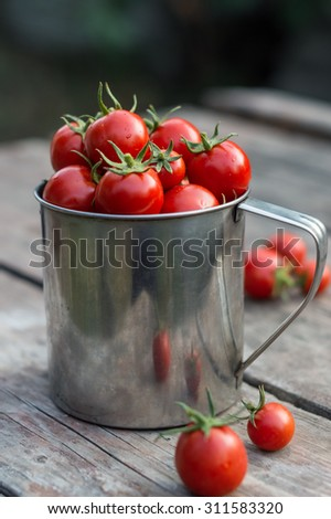 ripe cherry tomatoes on a wooden table in rustic iron mug - stock photo