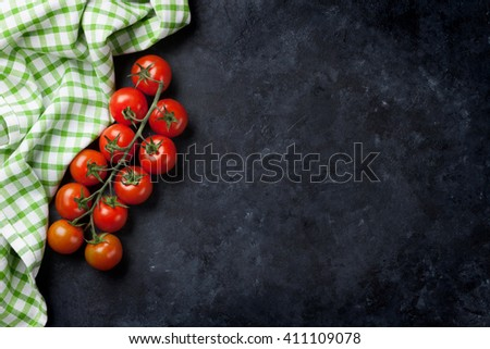 Ripe cherry tomatoes over stone kitchen table. Top view with copy space - stock photo