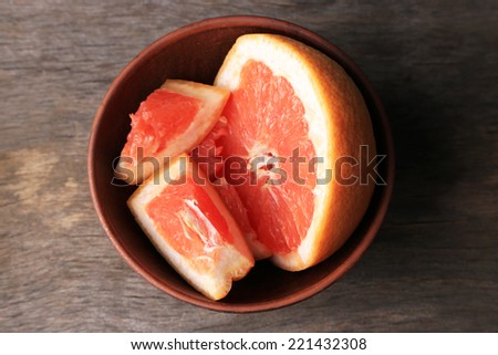 Ripe chopped grapefruit  in bowl, on wooden background - stock photo