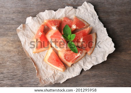 Ripe chopped grapefruit with mint leaves on wooden background - stock photo