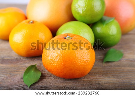 Ripe citrus with green leaves on wooden background - stock photo