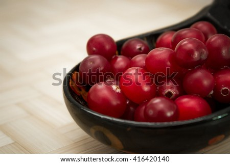Ripe cranberries, rolled in a wooden spoon. - stock photo