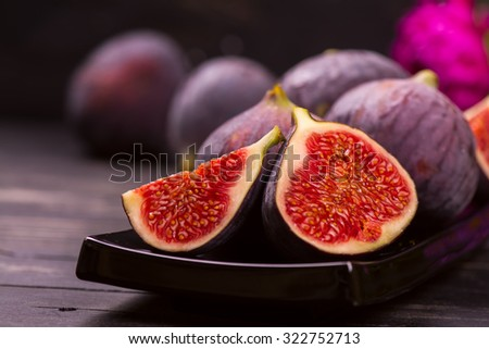 Ripe delicious figs and autumn flowers on black wooden background. Selective focus