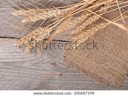 ripe ears of wheat on the old wooden background - stock photo