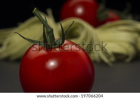 Ripe farm fresh juicy tomato with a green stalk for cooking in an Italian pasta recipe on a dark kitchen counter - stock photo