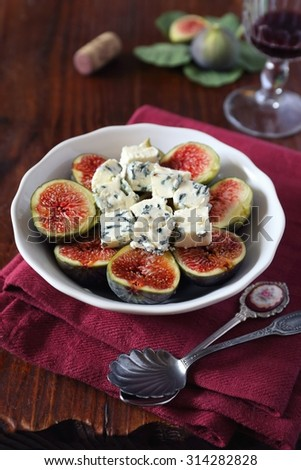 Ripe figs, blue cheese and glass of red wine on old wooden table  - stock photo