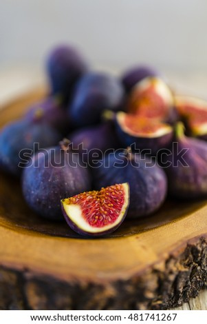 Ripe figs in a rustic wooden bowl on gray background.