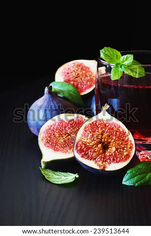 ripe figs, mint leaves and fruit drink on a black background.health and diet food. selective focus - stock photo