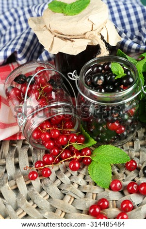 Ripe forest berries in glass jar and tasty jam on wooden background - stock photo