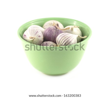 Ripe fragrant garlic in green bowl isolated on white close up