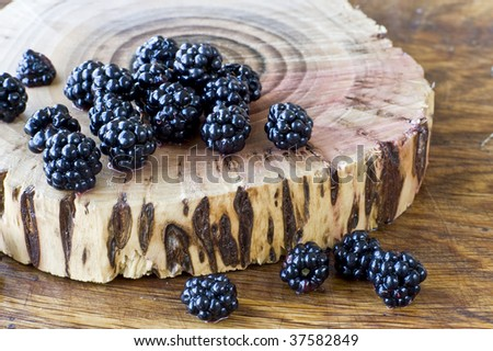 Ripe fresh blackberry scattered on the stump - stock photo