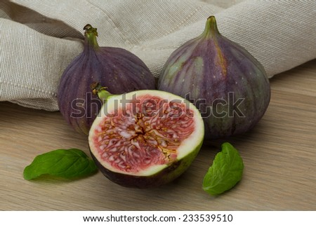 Ripe fresh Figs on the wooden background with mint leaves - stock photo