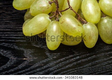 Ripe fresh juicy grape on a black table or board like background. - stock photo