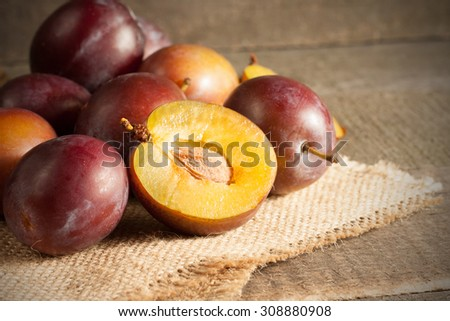 ripe, fresh, juicy plums on a dark wood background. - stock photo