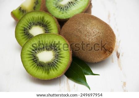 Ripe fresh kiwi on a white wooden background - stock photo