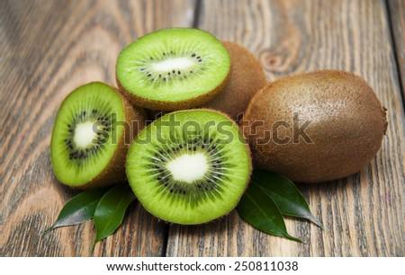 Ripe fresh kiwi on wooden background - stock photo