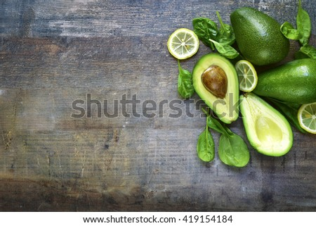 Ripe fresh organic avocado with baby spinach leaves and lemon slices on a rustic wooden background.Top view. - stock photo